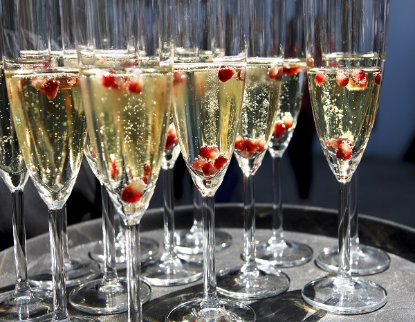 Sparkling champagne flutes on tray with pomegranate seeds.