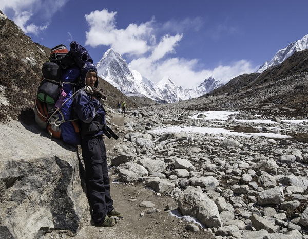 Sherpa carrying expedition kit Himalaya mountain peak Nepal